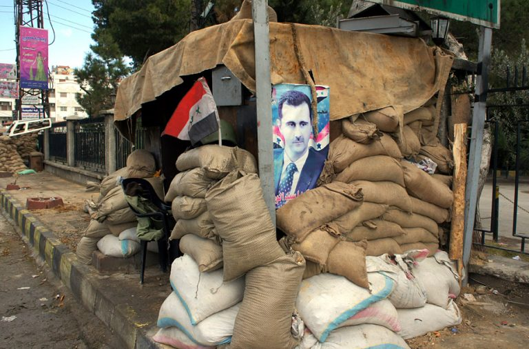 Hunkering down: a poster of Syria's president at a checkpoint on the outskirts of Damascus, Jan. 14 2012. (E. Arrott/VOA)